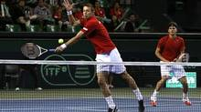 Canada's Daniel Nestor, left, hits a return beside his compatriot Frank Dancevic during their Davis Cup world group first round tennis doubles match against Japan's Kei Nishikori and Yasutaka Uchiyama in Tokyo Feb. 1, 2014. (YUYA SHINO/REUTERS)