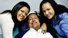 Venezuela's President Hugo Chavez smiles in between his daughters, Rosa Virginia, right, and Maria while recovering from cancer surgery in Havana in this photograph released by the Ministry of Information on Feb. 15, 2013. Venezuela's government published the first pictures of cancer-stricken Chavez since his operation in Cuba more than two months ago, showing him smiling while lying in bed reading a newspaper, flanked by his two daughters. The 58-year-old socialist leader had not been seen in public since the Dec. 11 surgery, his fourth operation in less than 18 months. The government said the photos were taken in Havana on Feb. 14, 2013 (Handout/Reuters)