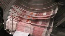 A machine counts and sorts out euro notes at the Belgian Central Bank in Brussels. (YVES HERMAN/YVES HERMAN/REUTERS)