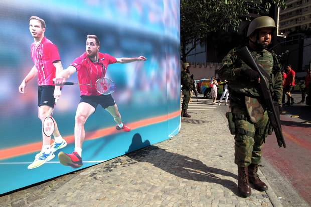 Soldiers patrol past a poster promoting the Olympics on Rio de Janerio's iconic Copacabana Beach on July 30, 2016.