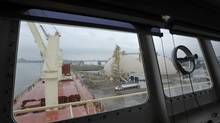 A cargo ship is loaded with soybeans at the Parrish & Heimbecker grain terminal in the port of Hamilton, Ont., with U.S. Steel (formerly Stelco) in the rear, as seen through the bridge windows Sept. 30, 2013. (J.P. MOCZULSKI For The Globe and Mail)