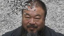 Chinese artist Ai Weiwei throws porcelain sunflower seeds into the air as he poses for a photograph with his new installation entitled 'Sunflower Seeds', at its unveiling in the Turbine Hall at the Tate Modern gallery, in London, October 11, 2010. (� Stefan Wermuth / Reuters/REUTERS)