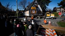 People watch as one of two heritage homes is moved to a new lot in the Kerrisdale neighbourhood of Vancouver, B.C., on Monday March 17, 2014. Two homes built in 1931 that were on separate lots were relocated to a new location a few blocks away where they will sit side-by-side and become part of a redevelopment that will include two new townhouses. The properties the houses were located on were purchased by two separate buyers with the intention of tearing them down and building new homes. Because they were designated as heritage homes, demolishing them wasn't an option. (DARRYL DYCK/THE CANADIAN PRESS)