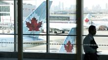 A person walks by Air Canada planes at Toronto Pearson Airport on Friday, April 13, 2012. (Michelle Siu/Michelle Siu/THE CANADIAN PRESS)