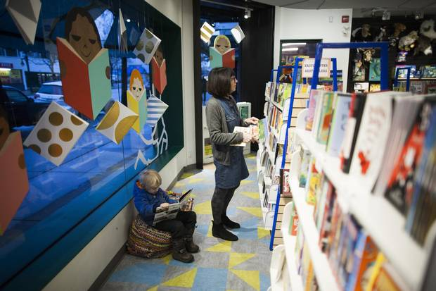 Phyllis Simon, right, co-owner of Kidsbooks, searches through books for a customer as Cillian Bird, 4, reads a book at her store.