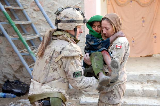 Ms. Le Scelleur (right) tends to a young Afghan girl suffering from a burn at a free medical clinic run by Afghan, Canadian and US medical and dental personnel in Spin Boldak, Afghanistan.