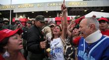 Supporters of Venezuela's President Hugo Chavez react to the news of his death outside the hospital in Caracas. (Fernando Llano/AP)