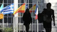 Pedestrians walk near the Greek, Spanish and French national flags outside the European Parliament in Brussels ahead of an EU informal heads of state summit . (FRANCOIS LENOIR/REUTERS)