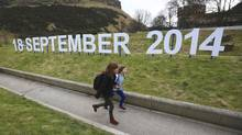 A teacher and schoolgirl run in front of a sign indicating the date of Scotland's independence referendum outside the Scottish Parliament in Edinburgh, March 21, 2013. (DAVID MOIR/REUTERS)