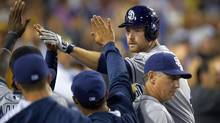 FILE - In this July 10, 2014, file photo, San Diego Padres' Chase Headley, right, is congratulated by teammates after hitting a solo home run during the sixth inning of a baseball game against the Los Angeles Dodgers in Los Angeles. (Mark J. Terrill/AP)