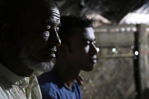 Abul Taher sits with his son Muhammad Selim, who left Bangladesh earlier this year as part of a tide of people seeking better prospects in Malaysia. When Mr. Selim was at sea, traffickers extorted money from his family and killed other passengers on his boat. He eventually landed in Indonesia but was returned to Bangladesh.
