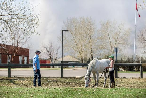 With smoke from wildfires several kilometres away, Sarah Naugle walks her horse Lady on the grounds of Greely Road School in the Gregoire subdivision on Monday. Aircraft dropping fire retardant are working with crews on the ground to protect homes from an uncontrolled wildfire close to the city.