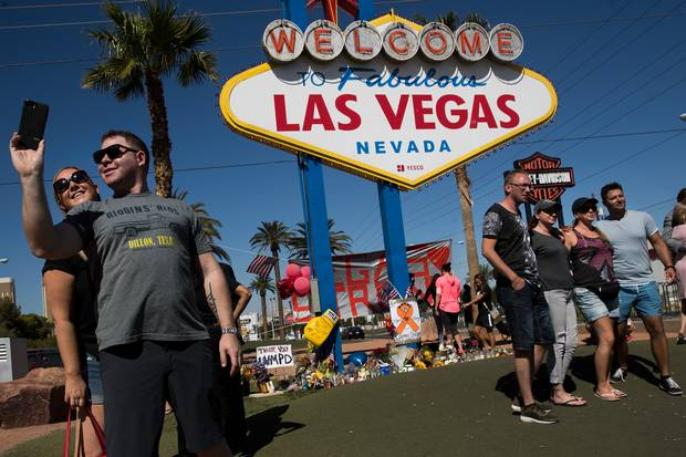 With a small makeshift memorial for Sunday's mass shooting victims below the 'Welcome to Fabulous Las Vegas' sign, visitors pose for photos by the iconic sign at the south end of the Las Vegas Strip on Oct. 5, 2017.