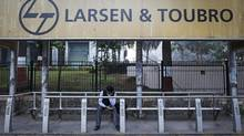 A man waits at a bus-stop with an advertisement of Larsen & Toubro outside the company's manufacturing unit in Mumbai, January 22, 2014. (Danish Siddiqui/Reuters)