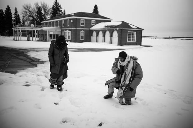 Lul Abdi Ali and Abdullahi Warsame climb through deep snow at the border.