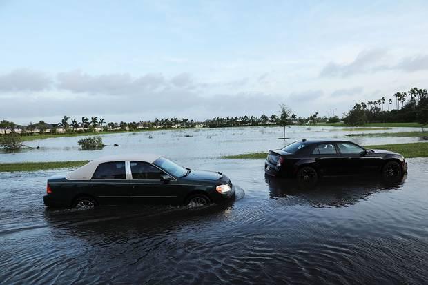 Bonita Springs, Fla., Sept. 11: Cars make their away through a flooded street.