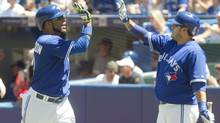 Toronto Blue Jays Edwin Encarnacion (left) high fives teammate Dioner Navarro in the on deck circle after scoring on a hit by Juan Francisco during first inning AL baseball game action against the Kansas City Royals in Toronto May 31, 2014. (FRED THORNHILL/THE CANADIAN PRESS)