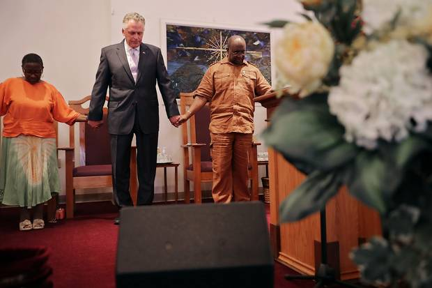 Virginia Gov. Terry McAuliffe holds hands and prays with Dr. Alvin Edwards, pastor of Mt. Zion First African Baptist Church, Aug. 13, 2017 in Charlottesville.