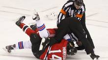 New York Rangers' Ryan McDonagh and New Jersey Devils' Adam Henrique (14) fight during the first period in Game 4 of their NHL Eastern Conference Final hockey playoff game