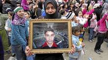A demonstrator holds a picture of a missing relative during a protest against Syria's President Bashar al-Assad in Baba Amro, near Homs, in this handout picture received on Jan. 22, 2012. (Reuters/Reuters)