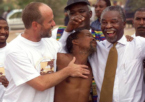 San tribe headman David Krupier, middle, thanks South African deputy president Thabo Mbeki, right, and agriculture minister Derek Hanekom, left, after the 1999 land-claim signing ceremony in San ancestral lands in the Kalahari Desert.
