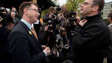 NDP Leader Adrian Dix, left, talks with Education Minister and Liberal candidate for Comox Valley Don McRae after McRae showed up at Dix's campaign stop in Comox, B.C., on April 18, 2013. (Darryl Dyck/The Canadian Press)