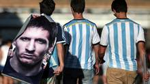 Argentina fans carry a poster of Lionel Messi while leaving the National Stadium where they watched Argentina beat Belgium in the 2014 World Cup quarter-finals in Brasilia, July 5, 2014. (STRINGER/BRAZIL/REUTERS)