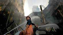 A firefighter works to contain a blaze at CentralWorld shopping centre in Bangkok on Thursday. Wednesday's violence saw government forces evict Red Shirt protesters from the city's major shopping district. (Paula Bronstein/Getty Images)