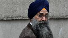 Inderjit Singh Reyat, the only man ever convicted in the Air India bombings of 1985, waits outside B.C. Supreme Court during a fire drill which forced everyone in the building outside prior to the start of the second day of his perjury trial in Vancouver on Sept. 10, 2010. (Darryl Dyck/The Canadian Press)