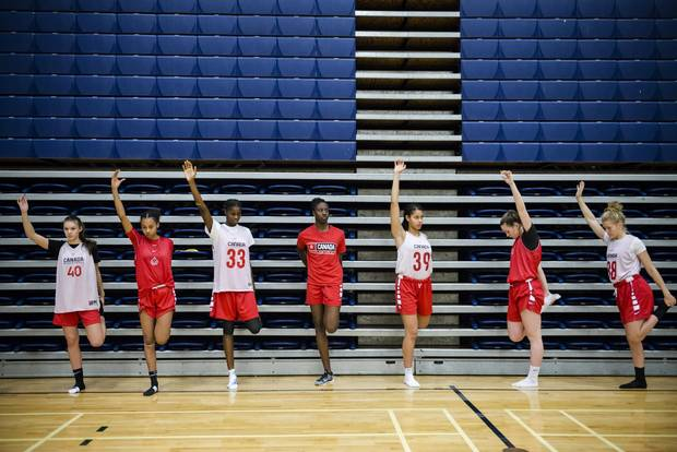 Laeticia Amihere, centre, joins other athletes in a stretch during Canada Basketball camp at Humber College in Toronto on Dec. 15, 2017.