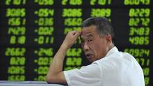 An investor looks back in front of an electronic board showing stock information filled with green-coloured figures, which indicate falling prices, at a brokerage house in Fuyang, Anhui province June 20, 2013. (Reuters/China Daily)