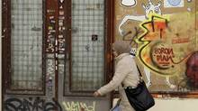 In this photo taken Saturday, April 14, a woman walks past a closed store in Madrid, Spain, Saturday, April 14, 2012. (Alberto Di Lolli/AP)