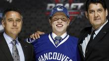 Hunter Shinkaruk poses with team executives (Reuters)
