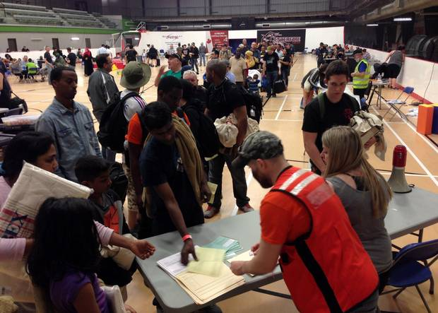 Evacuees from Fort McMurray, Alta., line up to register at an evacuee reception centre in nearby Anzac, Alta., on Wednesday.