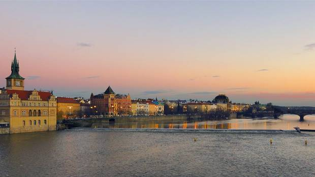 The sun sets over the Vltava River in Prague, Czech Republic.