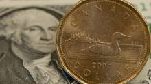 A Canadian dollar, or loonie, sits on top of its American counterpart. (THE CANADIAN PRESS/Adrian Wyld)