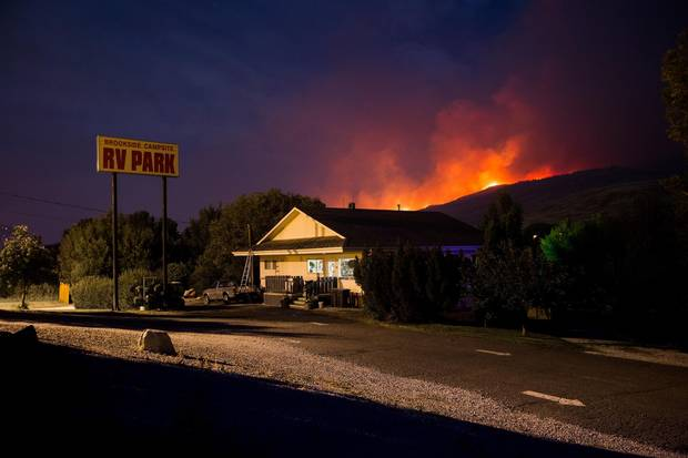 A wildfire burns on a mountain behind an RV park office in Cache Creek, B.C. in the early morning hours of Saturday, July 8, 2017.