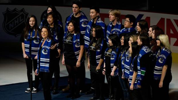 Recording artist Sarah McLachlan, second left, sings the Canadian and American national anthems with students from her music school before the Vancouver Canucks and Anaheim Ducks play their season opening game on Jan. 19, 2013. (DARRYL DYCK/THE CANADIAN PRESS)
