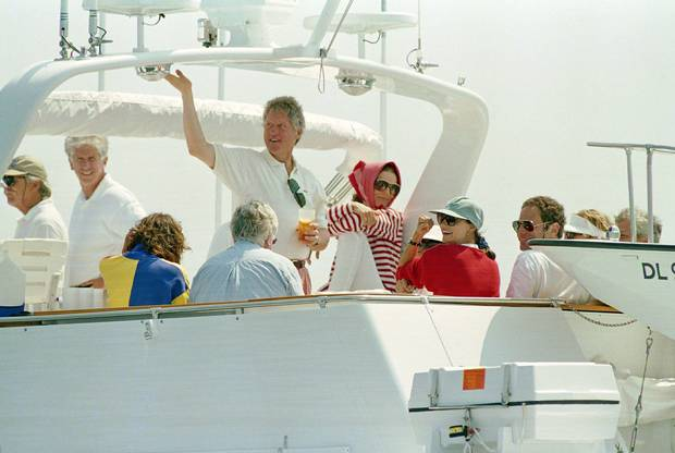 Aug. 23, 1993: President Clinton waves from the top of the cruise boat Relemar with Jackie Kennedy Onassis, middle right wearing a scarf, and other Clinton and Kennedy family members in Vineyard Sound off the coast of Martha's Vineyard, as guests of Onassis for a lunchtime cruise.