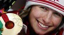 Canada's Chandra Crawford presents her gold medal after winning the women's sprint cross-country skiing race at the Torino 2006 Winter Olympic Games in Pragelato, Italy, February 22, 2006. (Reuters)