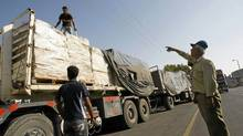 Palestinian workers inspect trucks carrying supplies after it arrived in Rafah town through the Kerem Shalom crossing between Israel and the southern Gaza Strip on Jun 16, 2010. (SAID KHATIB/AFP/Getty Images)