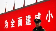 A paramilitary policeman stands guard in front of a screen displaying propaganda slogans on Beijing's Tiananmen Square November 6, 2012 as security is tightened around the square and the adjoining Great Hall of the People. (DAVID GRAY/REUTERS)