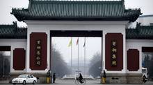 A man rides a bicycle past the entrance of Shougang Group on the outskirts of Beijing March 29, 2010. (JASON LEE/Jason Lee/Reuters)