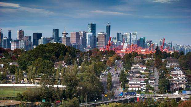 The downtown skyline and cranes at Port Metro Vancouver are seen in the distance behind houses in east Vancouver.