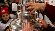 Members of the Vancouver Angels novice C1 girls minor hockey team touch the Stanley Cup after they were surprised with it before their practice on Dec. 7, 2012. (Darryl Dyck/The Canadian Press)