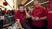 Mark Wahlberg, left, and former NHL player Tie Domi take donations during CIBC Miracle Day on CIBC's trading floor in Toronto on Wednesday, Dec. 5, 2012. Money raised from CIBC clients goes towards children's charities in Canada. (Matthew Sherwood for The Globe and Mail)