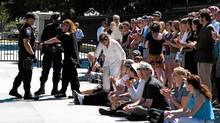 Canadian actress Margot Kidder, left, is handcuffed by police as other environmentalists applaud outside the White House Aug. 23, 2011. THE CANADIAN PRESS/Keith Lane (Keith Lane/The Canadian Press)