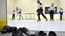 Dress shoes sit rinkside as IT Weapons Inc. employees warm up to play some hockey on the company's indoor plastic hockey rink in their Brampton offices (J.P. MOCZULSKI)