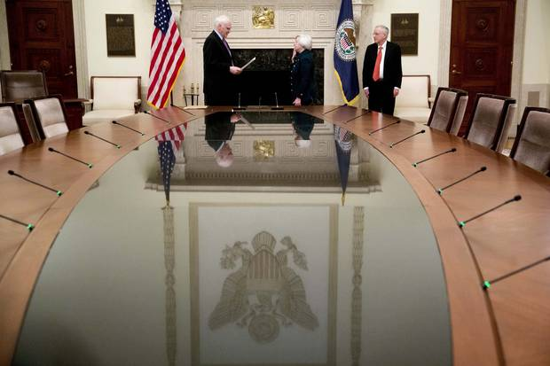 Janet Yellen, chair of the U.S. Federal Reserve, takes the oath of office in 2014. Her husband, George Akerlof, right, looks on.
