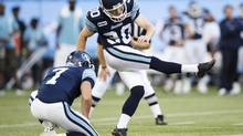 Toronto Argonauts' Swayze Waters kicks a field goal beside place holder Trevor Harris (L) against the Winnipeg Blue Bombers during the first half of their CFL in Toronto, July 18, 2012. (MARK BLINCH/REUTERS)